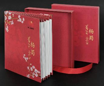 Red photobook, floral print cover, and pink flower bouquet.